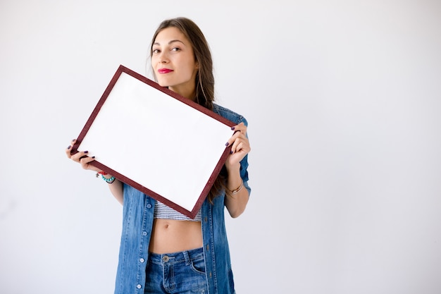 La ragazza allegra tiene un cartello o un manifesto bianco in bianco