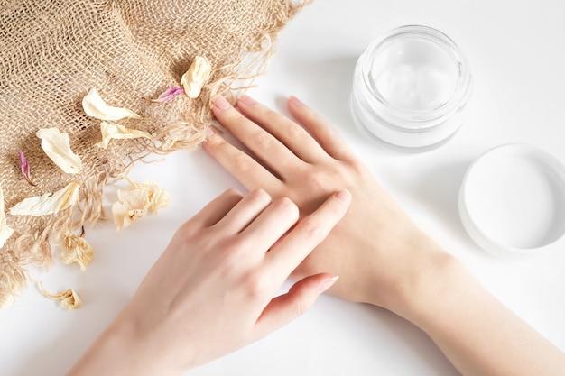 La ragazza applica crema idratante per le mani su un muro bianco con petali di fiori secchi e tela. crema ecologica senza profumo naturale. mani femminili con un barattolo di crema su una parete leggera