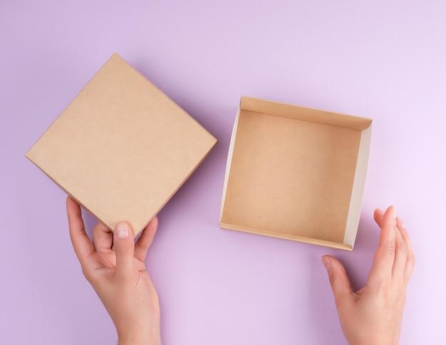La ragazza apre una scatola quadrata marrone su uno sfondo viola