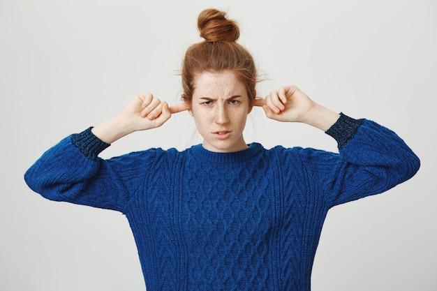 La ragazza arrabbiata della testarossa ha chiuso le orecchie riluttanti ad ascoltare