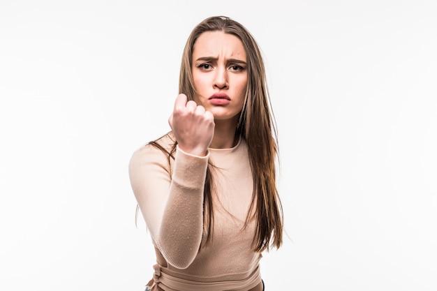 La ragazza arrabbiata mostra il pugno sulla macchina fotografica isolata su bianco