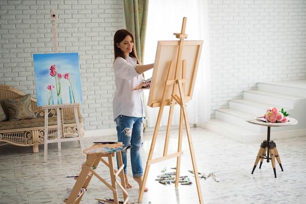 La ragazza artista dipinge su tela su cavalletto. modella in studio