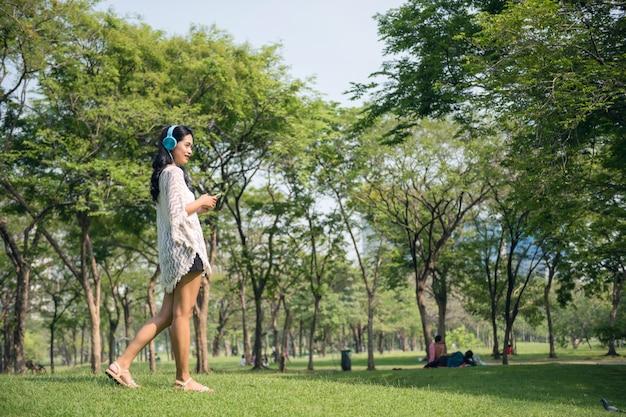 La ragazza asiatica ascolta musica in parco