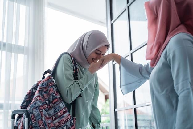 La ragazza asiatica bacia la mano di sua madre