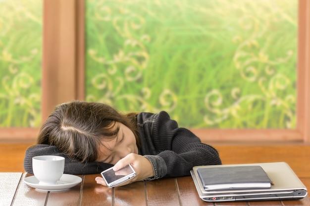 La ragazza asiatica che dorme e tiene lo smartphone a disposizione