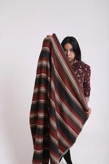 La ragazza asiatica copre il viso con un fazzoletto su sfondo bianco. bella bruna con una stola in faccia. vita religiosa, bellezza orientale