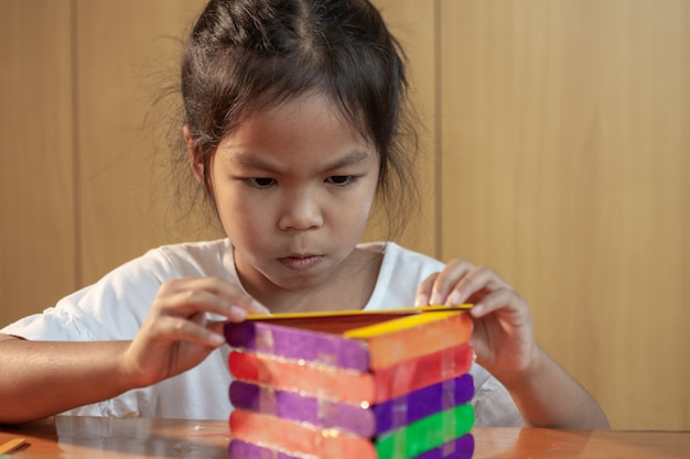 La ragazza asiatica del bambino che incolla il gelato colorato attacca dalla pistola per colla elettrica della colata a caldo. i bambini si divertono a fare casa su un progetto artigianale.