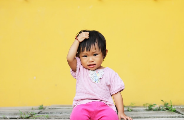 La ragazza asiatica del bambino del bambino ha messo la sua mano sulla sua testa.