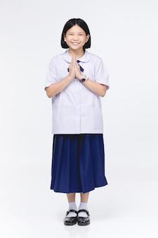 La ragazza asiatica del bambino in uniforme dello studente, comportandosi sawaddee significa ciao.