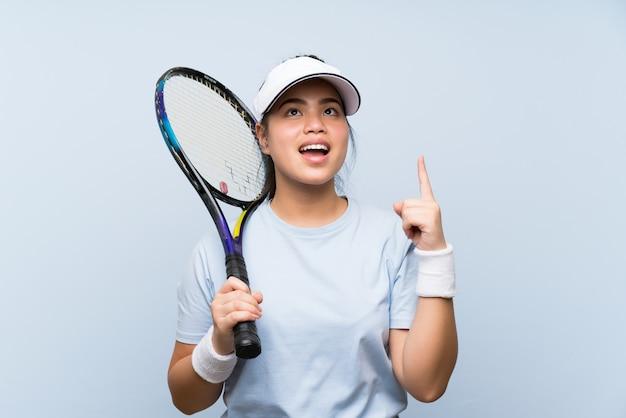 La ragazza asiatica del giovane adolescente che gioca a tennis che intende realizzare la soluzione mentre solleva un dito su
