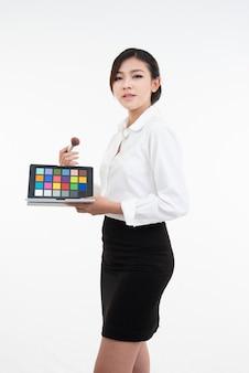 La ragazza asiatica del truccatore mostra i prodotti dei cosmetici, che sono stati fatti il trucco. il concetto di bellezza