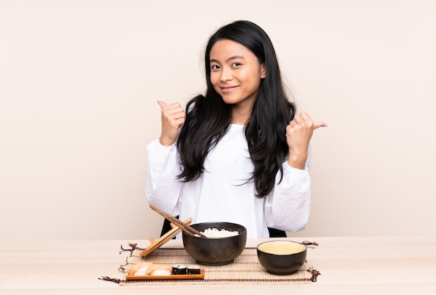 La ragazza asiatica dell'adolescente che mangia l'alimento asiatico isolata su fondo beige con i pollici aumenta il gesto e sorridere