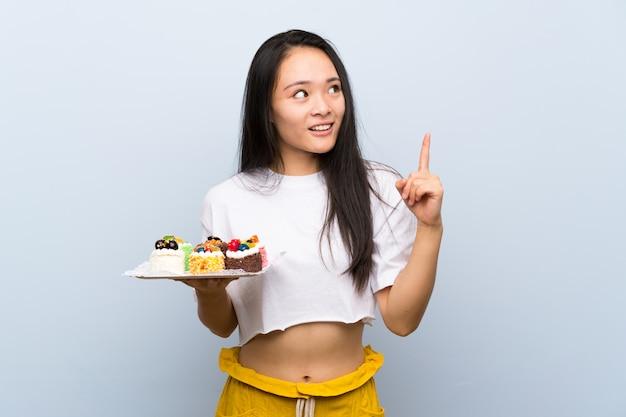 La ragazza asiatica dell'adolescente che tiene un sacco di mini torte differenti che intende realizzare la soluzione mentre solleva un dito su