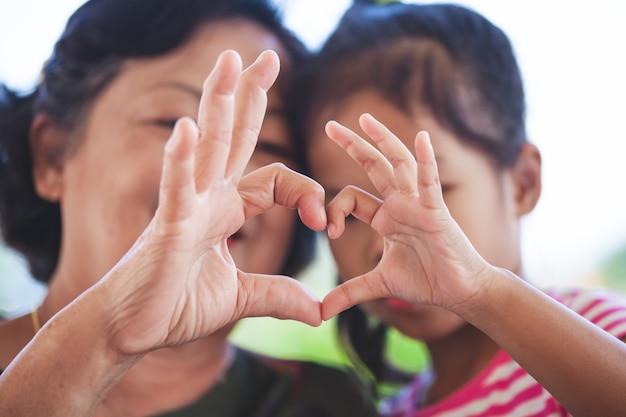 La ragazza asiatica della nonna e del piccolo bambino che fa il cuore modella con le mani insieme ad amore