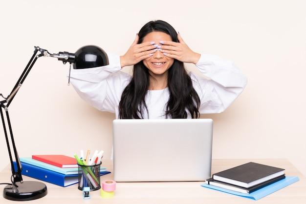 La ragazza asiatica dello studente in un posto di lavoro con un computer portatile isolato sul rivestimento murale beige osserva a mano