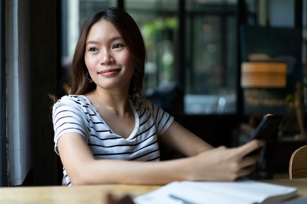 La ragazza asiatica di affari inizia a lavorare con il computer portatile al caffè