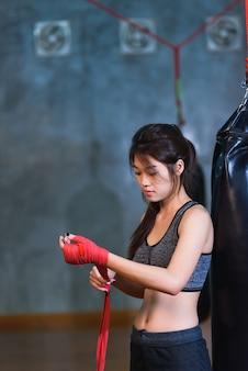 La ragazza asiatica di inscatolamento lega la fasciatura sulla sua mano