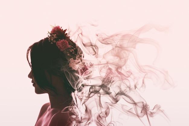 La ragazza asiatica è bella e affascinante con corona di fiori. sta evaporando nel fumo dei profumi. flare light style.