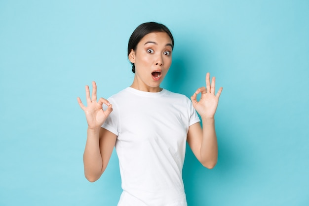 La ragazza asiatica eccitata e impressionata in maglietta bianca sembra sorpresa e stupita con un servizio fantastico e perfetto, mostra un gesto ok e sembra sbalordita sul muro blu