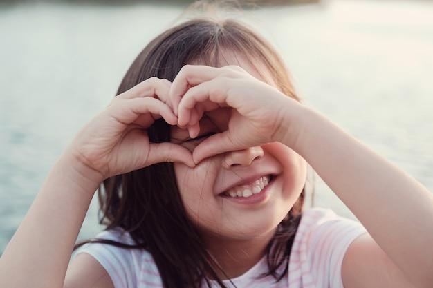 La ragazza asiatica felice che fa un cuore modella con le sue mani per salute del cuore e dare il concetto di donazione