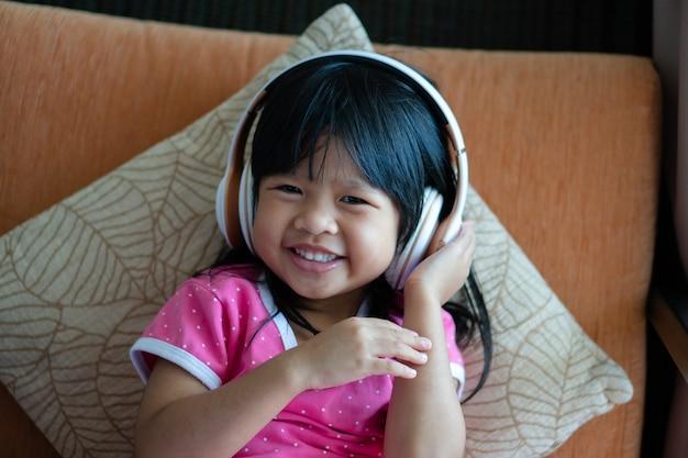 La ragazza asiatica felice che sorride e che gode ascolta la musica in cuffie sul salone del sofà