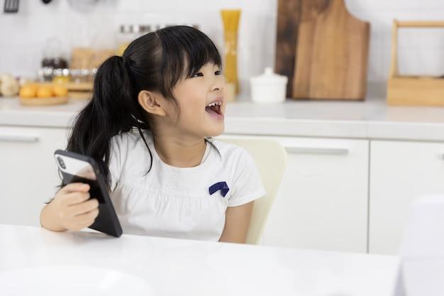 La ragazza asiatica felice gode dello smartphone