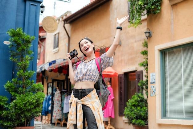 La ragazza asiatica gode felicemente di scattare foto in urbano mentre viaggia.