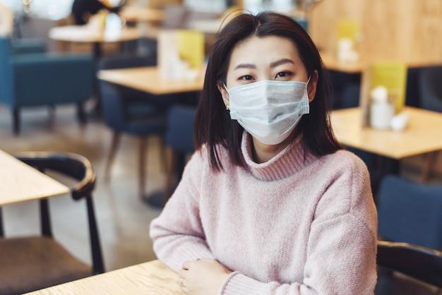 La ragazza asiatica in una maschera protettiva sta sedendosi in una scuola o in un caffè. una bella donna con una mascherina medica per non contrarre il virus. prevenzione delle malattie