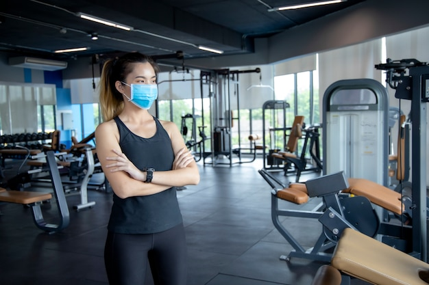 La ragazza asiatica indossa una maschera di anatomia per esercitarsi in palestra per evitare di credere ai virus