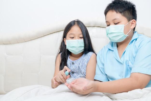 La ragazza asiatica indossa una maschera igienica e preme l'alcool spray sul fratello della mano