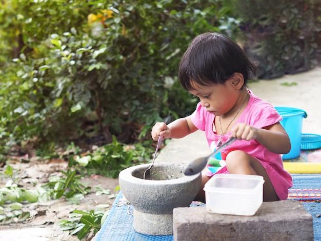 La ragazza asiatica scherza il gioco che cucina con il mortaio
