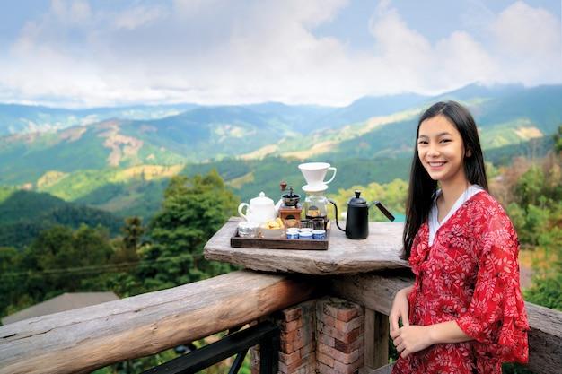 La ragazza asiatica si rilassa con il caffè caldo e l'insieme di tè caldo sul punto di vista di doi sakad