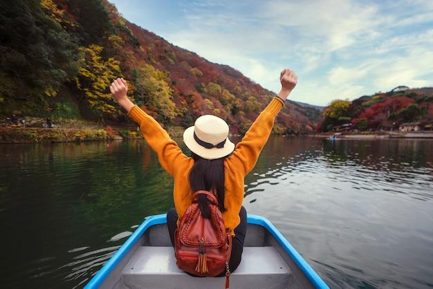 La ragazza asiatica si rilassa dalla pagaia e una barca di affitto sul fiume nel parco di arashiyama
