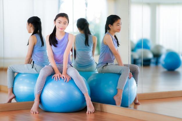 La ragazza asiatica si siede su una palla e si rilassa prima dell'esercizio