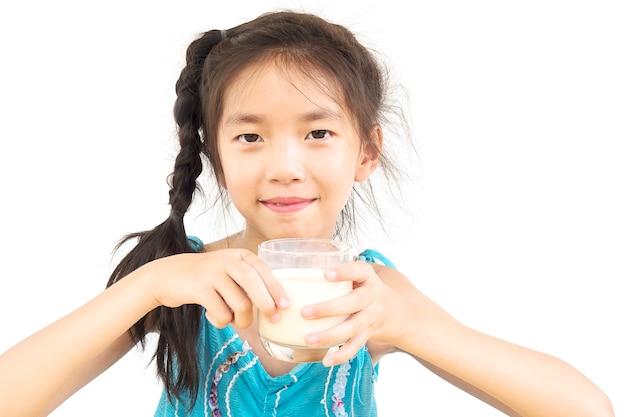 La ragazza asiatica sta bevendo un bicchiere di latte sopra fondo bianco