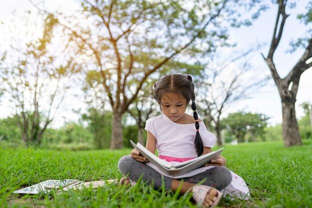 La ragazza asiatica sta leggendo un libro nel parco.