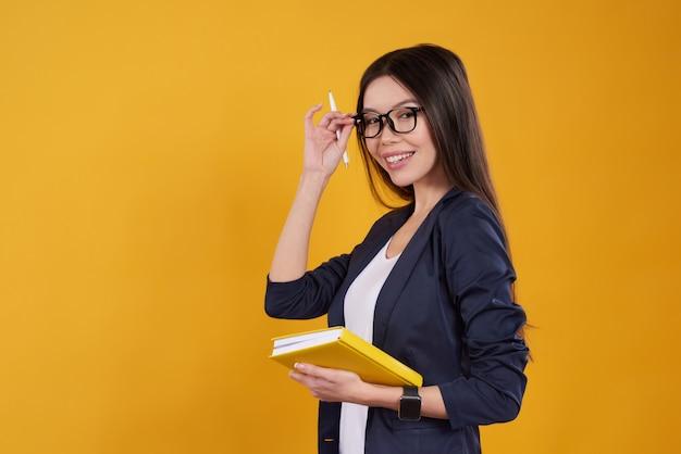 La ragazza asiatica sta posando prendendo le note con i vetri.