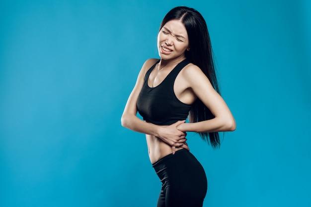 La ragazza asiatica sta soffrendo dalla distorsione posteriore.