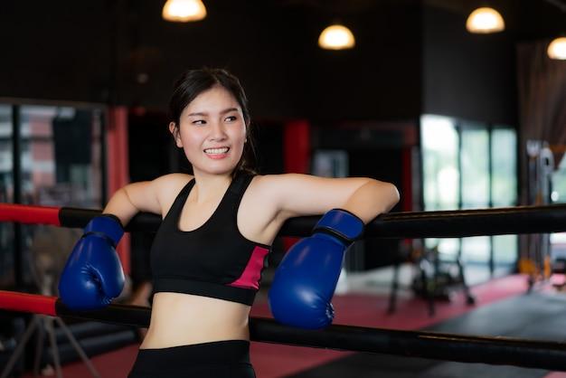 La ragazza asiatica stanca di sport del pugile si è appoggiata alle corde rosse nere sul ring e si riposa dopo un duro allenamento nella palestra del loft nero. vestibilità sportiva per stile di vita sano modello asiatico del concetto di palestra di boxe.
