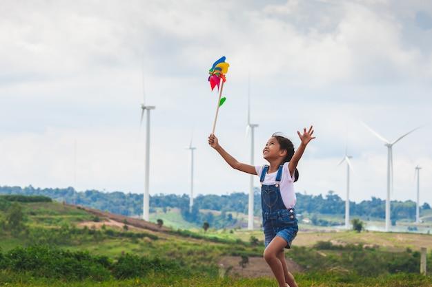 La ragazza asiatica sveglia del bambino sta correndo e giocando con il giocattolo del generatore eolico nel campo del generatore eolico