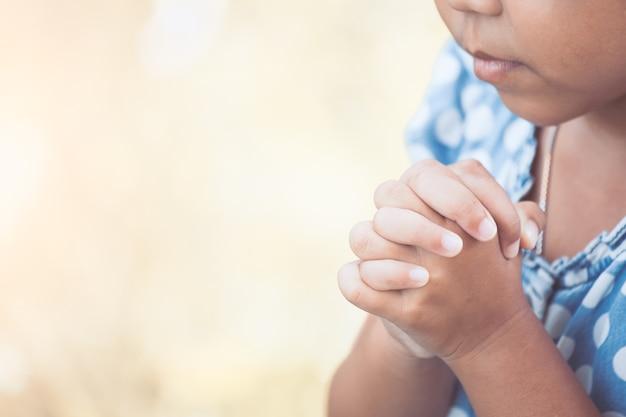 La ragazza asiatica sveglia del piccolo bambino che prega con ha piegato la sua mano per il concetto di fede, di spiritualità e di religione