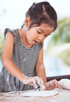 La ragazza asiatica sveglia del piccolo bambino prepara una pasta per i biscotti bollenti nella cucina