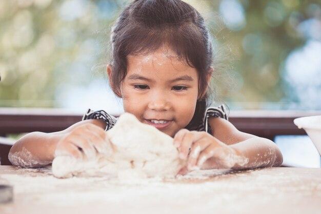 La ragazza asiatica sveglia del piccolo bambino prepara una pasta per i biscotti bollenti