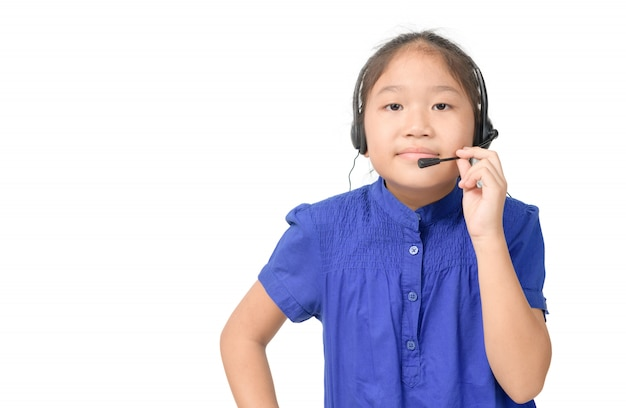La ragazza asiatica sveglia sta lavorando come operatore alla linea di assistenza che parla con il cliente facendo uso della cuffia avricolare,