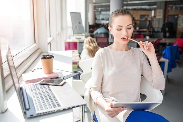 La ragazza astuta sta sedendosi vicino alla finestra nella stanza e sta guardando al tablet. sta masticando la matita. la ragazza sta studiando alcuni materiali e informazioni utili da esso.