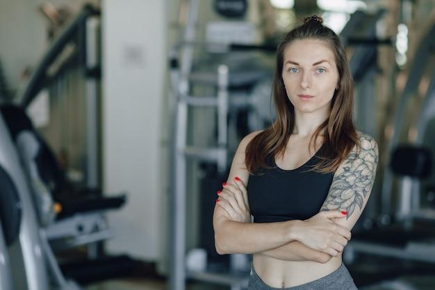 La ragazza atletica attraente sta sulla parete dei simulatori in palestra. uno stile di vita sano.