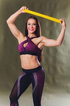 La ragazza atletica si esercita usando una banda di resistenza. foto della ragazza su fondo. forza e motivazione.