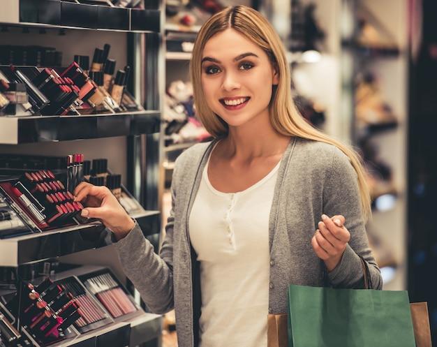 La ragazza attraente con i sacchetti della spesa sta scegliendo il rossetto