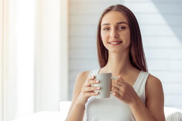 La ragazza attraente in maglietta giro collo bianca sta tenendo una tazza.