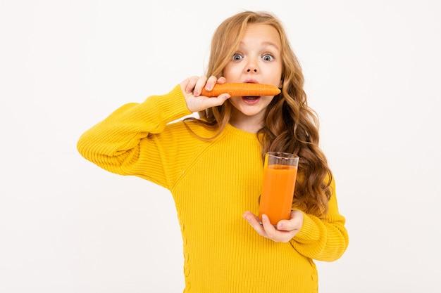 La ragazza attraente in vestiti gialli stuzzica una carota che tiene un vetro in sua mano con il succo di carota
